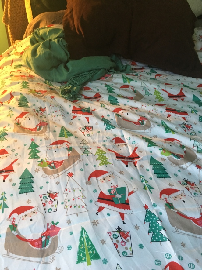 A thin white fabric has stylized trees and Santa's with red, teal, green and brown tress, presents and sleighs. It looks cheap and tacky and that makes Natalie love it more.