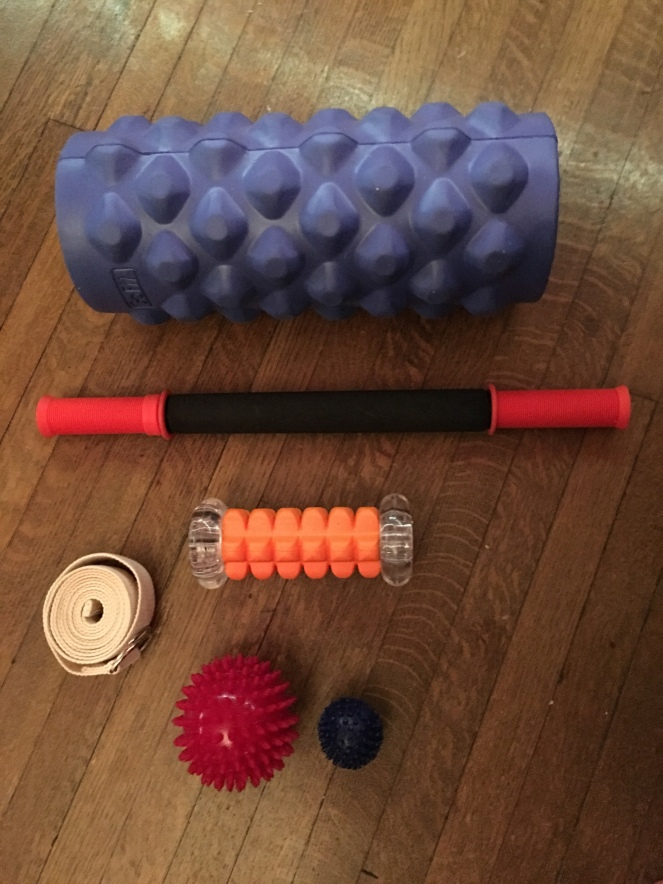 The picture is looking down at a hardwood floor that displays a large knobby foam roller, a thin rollin pin style roller, and a couple spikey balls
