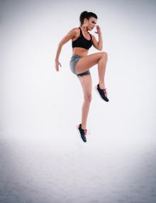 Woman in sports bra and shorts jumping