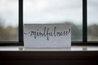 paper with the word mindfulness in calligraphy on a windowsill