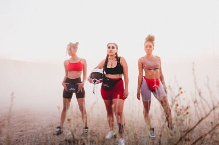 Three women in sports bras and bike shorts in the desert