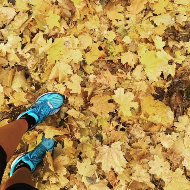 Image description: lower half of Tracy's legs in the bottom left corner of frame, running shoes, short socks, and capri tights, standing amongst a thick ground covering of fallen maple leaves.