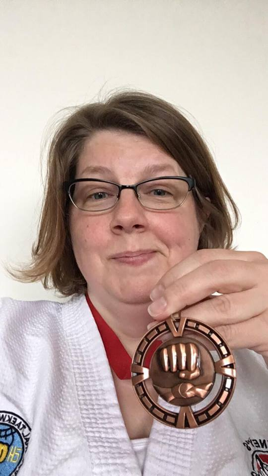 The author, a white woman in her mid-forties with shoulder length brown hair and glasses is wearing a martial arts uniform and holding a bronze medal.