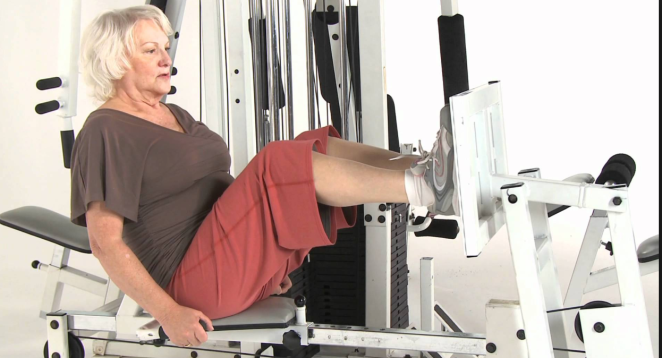 A woman doing leg presses on a leg press machine.