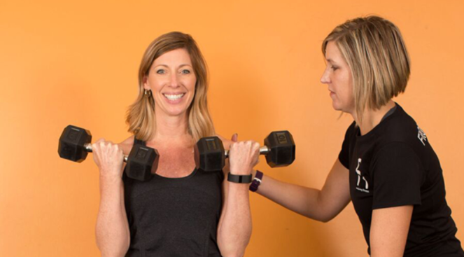 A woman lifting dumbbells, with another woman helping her with form.