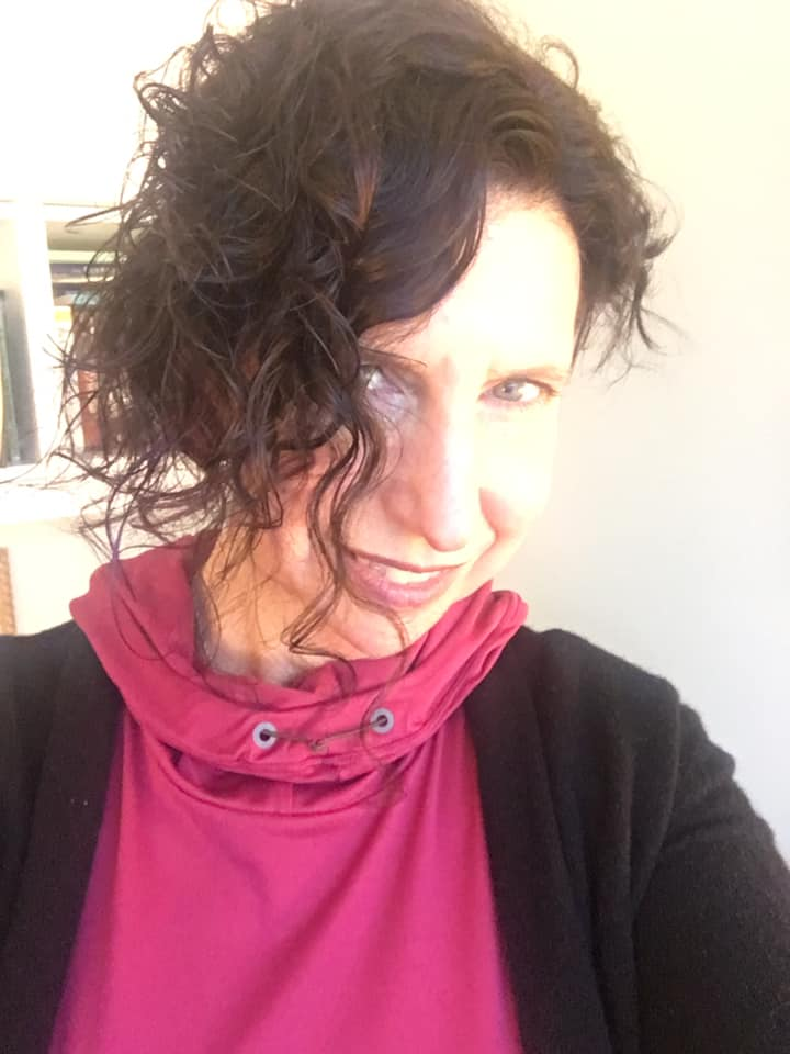 A white woman in a pink top with a black cardigan posing jauntily for the camera with her curly hair falling in front of her face