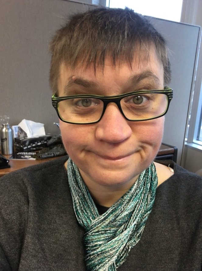 It's a selfie of Nat's face with a wry smile and slightly messy, short brown hair. She happens to be at her desk at work and trying not to let that bum her out too much.