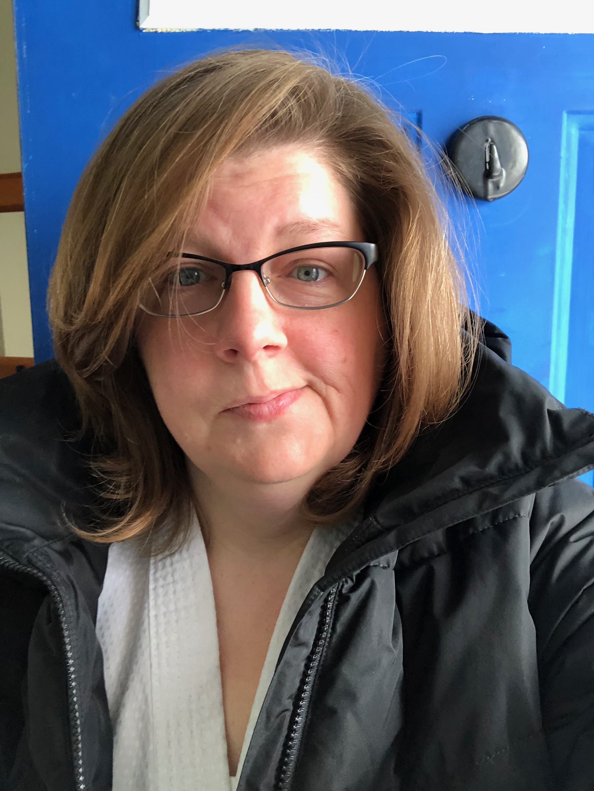 The author, a woman in her mid-forties with light brown shoulder length hair, is wearing glasses,  a black coat, and a white shirt. She is standing in front of a blue door and she looks nervous.