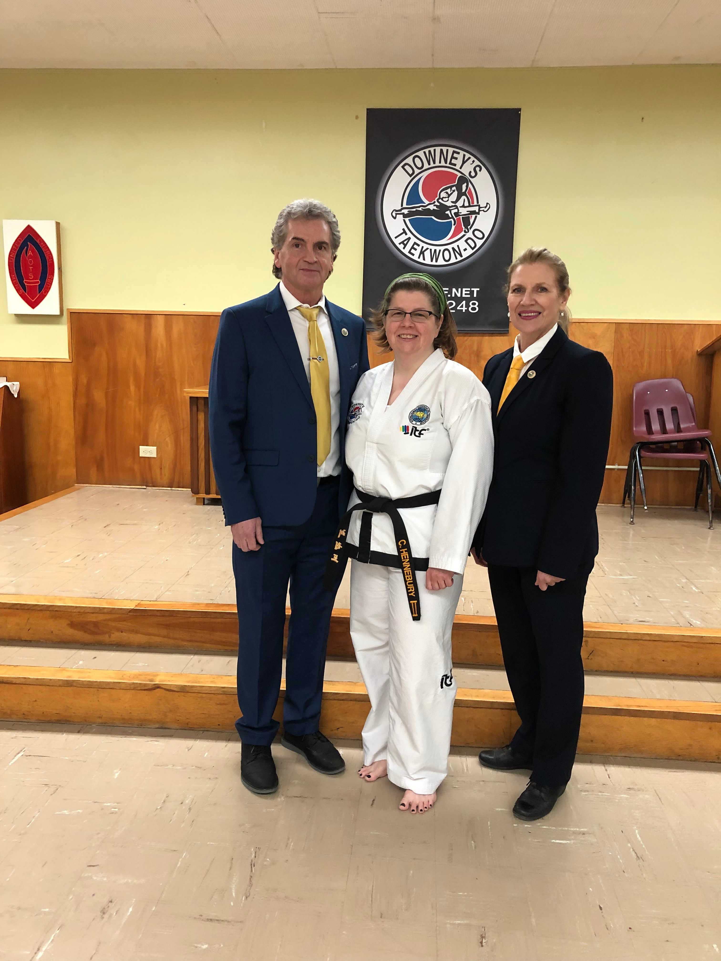 Three people stand in a gym, there is a black banner hanging on the wall behind them that reads 'Downey's Taekwon-Do' and features a graphic of a martial artist.   All three people are white, one man and one woman are wearing suits and they are standing on either side of a woman in a white martial arts uniform.