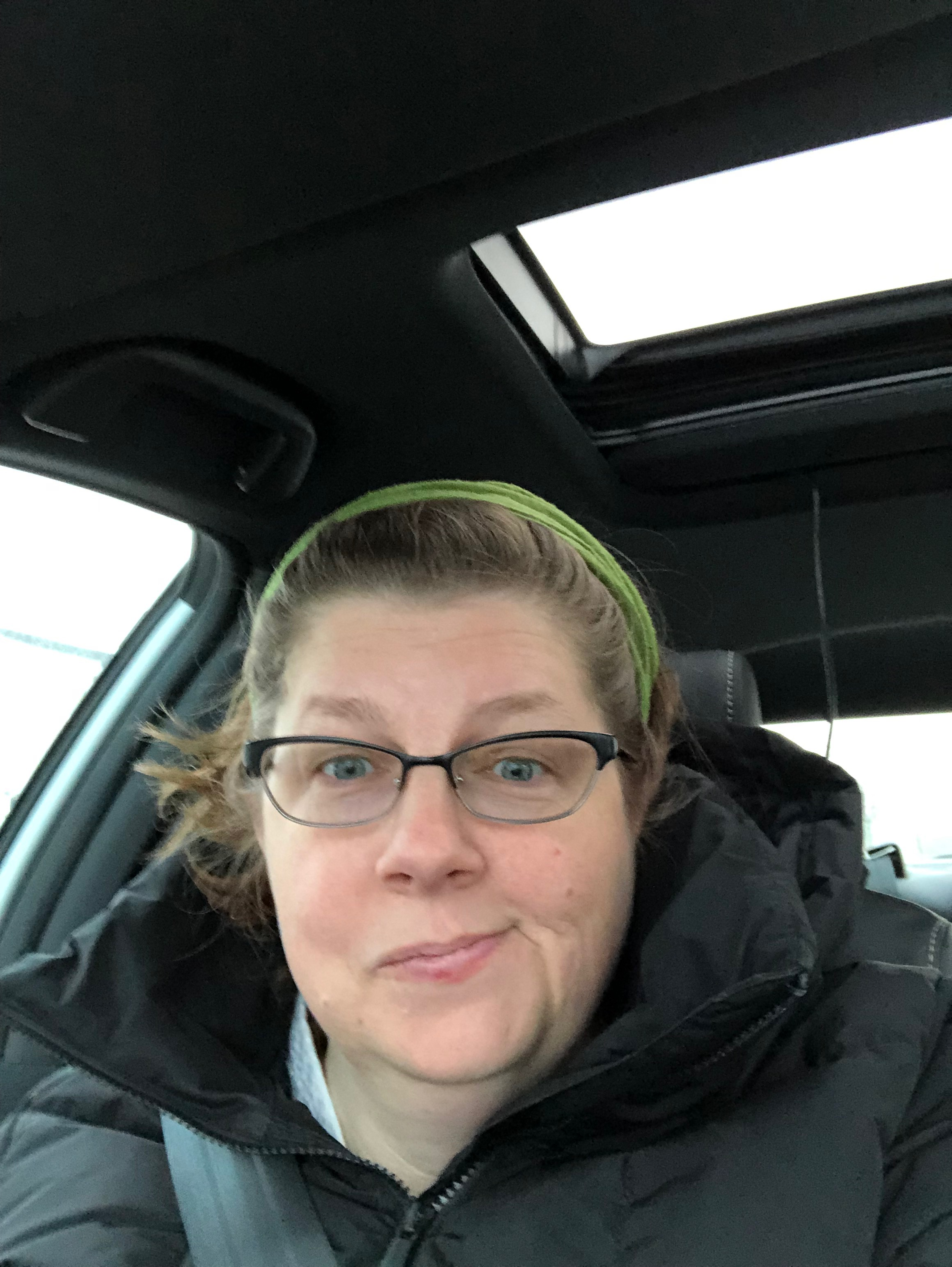 The author, a woman in her mid-forties, sits in the front passenger seat of a car. She has her brown hair back in a green bandana, she is wearing glasses and a black winter jacket, and she is smirking and looking pleased with herself.