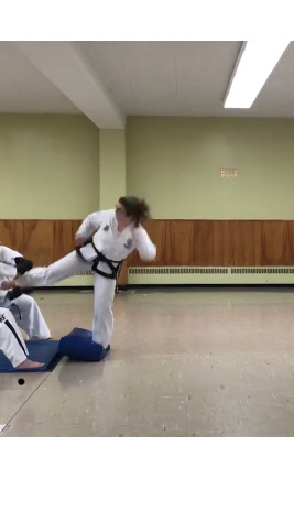 The author, in her white martial arts uniform, lands on a blue mat with her left foot as her right foot breaks a board held at hip height by two people in white uniforms.