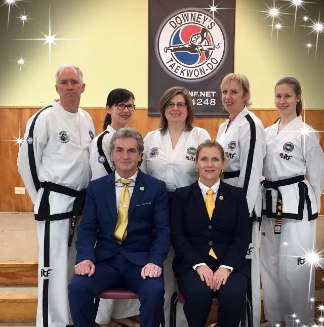 A group of martial artists are posing for a photo.  A man and a woman wearing suits are seated on chairs in front and one man and four women in white martial arts uniforms are standing behind them. There is a black banner hanging on the wall behind them that reads 'Downey's Taekwon-Do' and features a graphic of a martial artist.