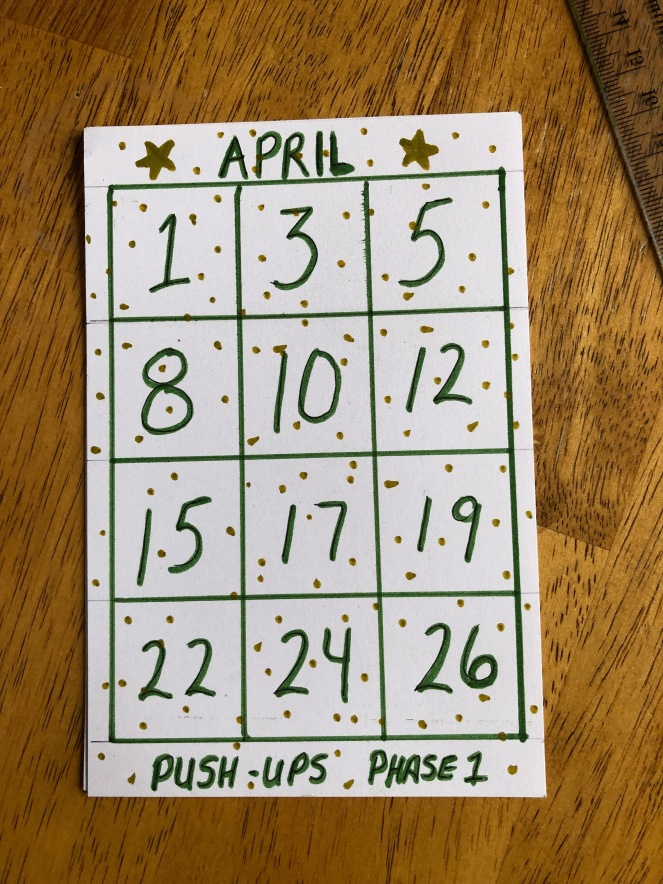 A rectangular white card covered in gold dots sits on a wooden surface. The card features a grid with 12 blocks, each block contains a date  written in green. The word April is at the top and the words Push-Ups Phase 1 are at the bottom.