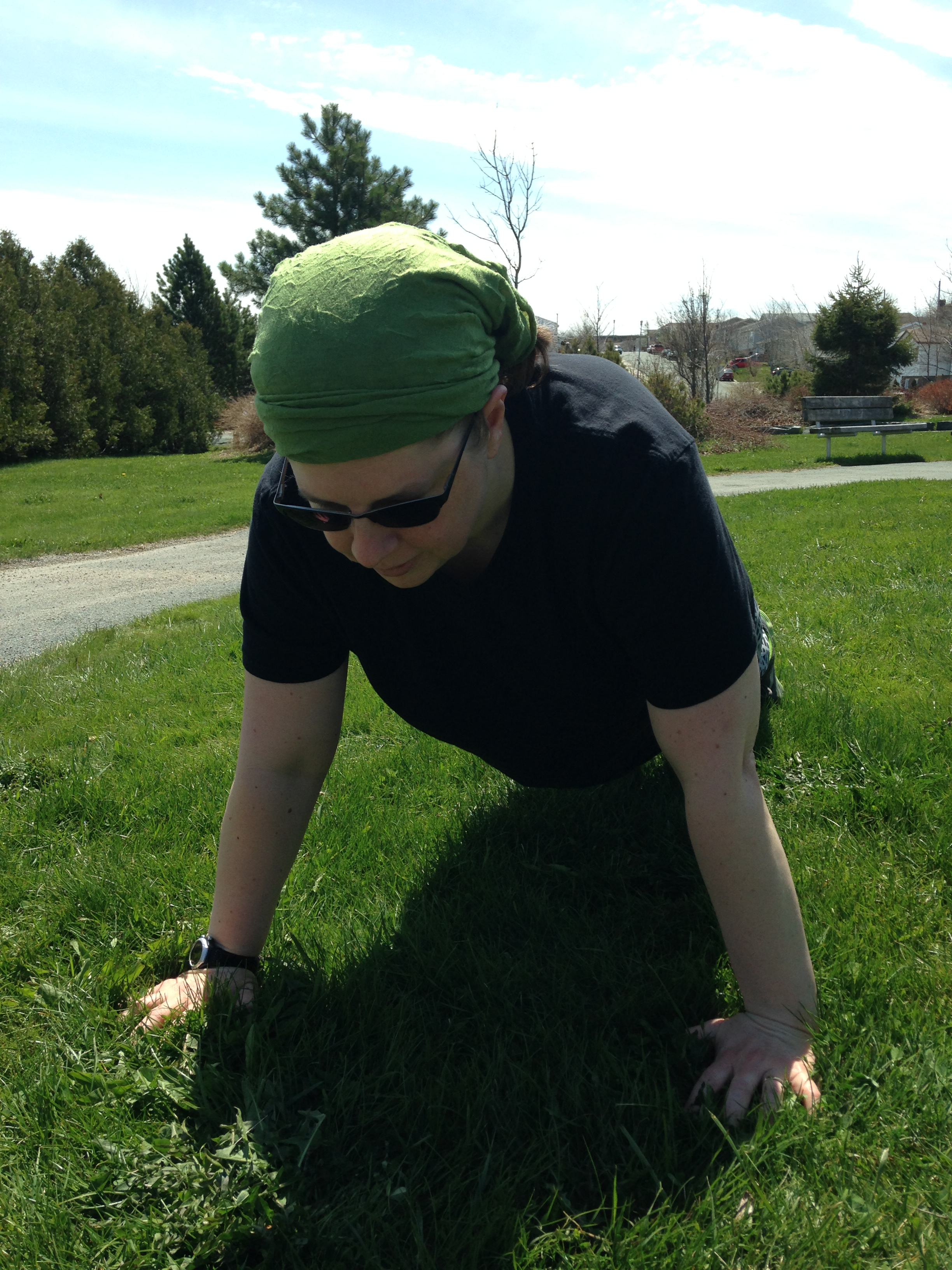 The author, wearing sunglasses, a green bandanna, a black shirt, and grey and black leggings, does a push-up on the grass in a field on a sunny day.