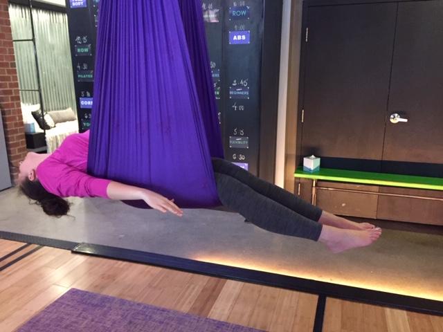 One of my classmates lying in a purple yoga hammock.