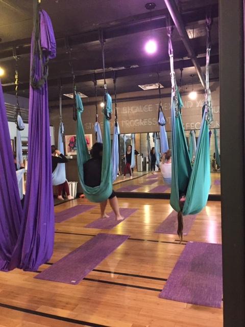 The yoga studio with an array of yoga hammocks, mats underneath them.