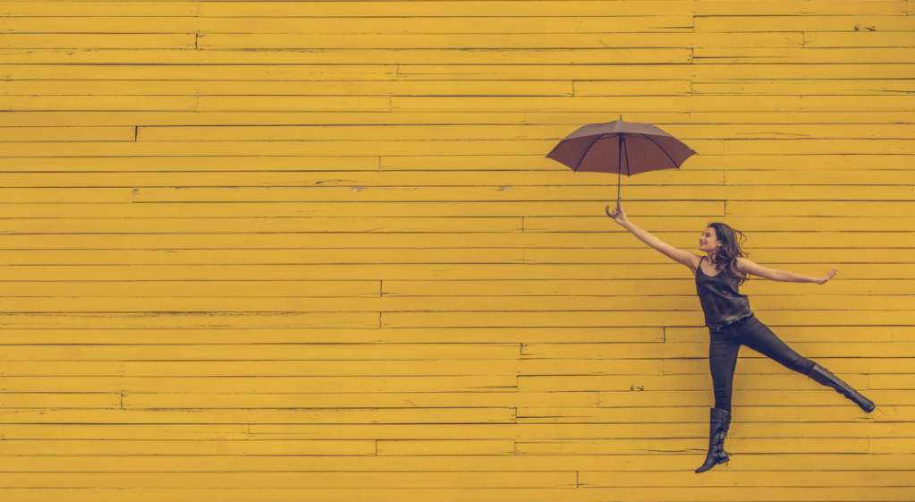 Woman leaping with an umbrella in front of a yellow wall.