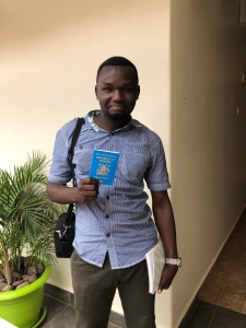 A young Ugandan man in a blue checked shirt smiling and holding a passport
