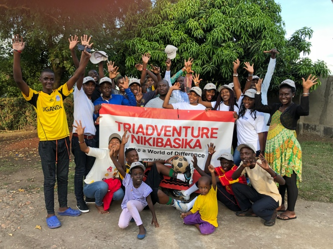 A large group of Ugandan adults and young people with their hands in the air and a Triadventure banner