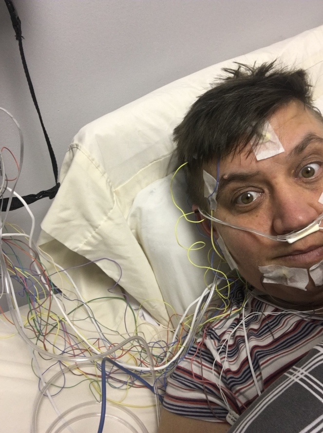 Natalie lies in bed with over 12 wires and sensors attached to her face, scalp and neck. There are two sensors up her nose. Her head is on a pillow and we can see the trail of wires going out of shot.