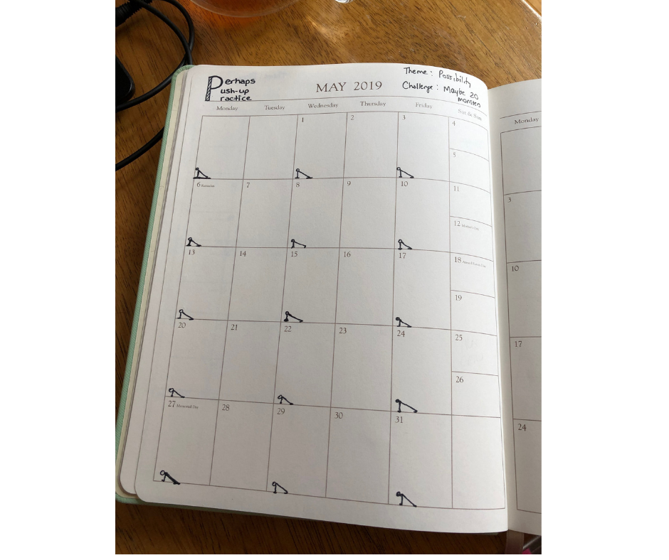 A paper calendar, open to May 2019, sits on a wooden surface. The words 'Perhaps Push-ups Practice' are written in black ink in one corner and there are stick figures doing push-ups drawn on Monday, Wednesday and Friday of each week.