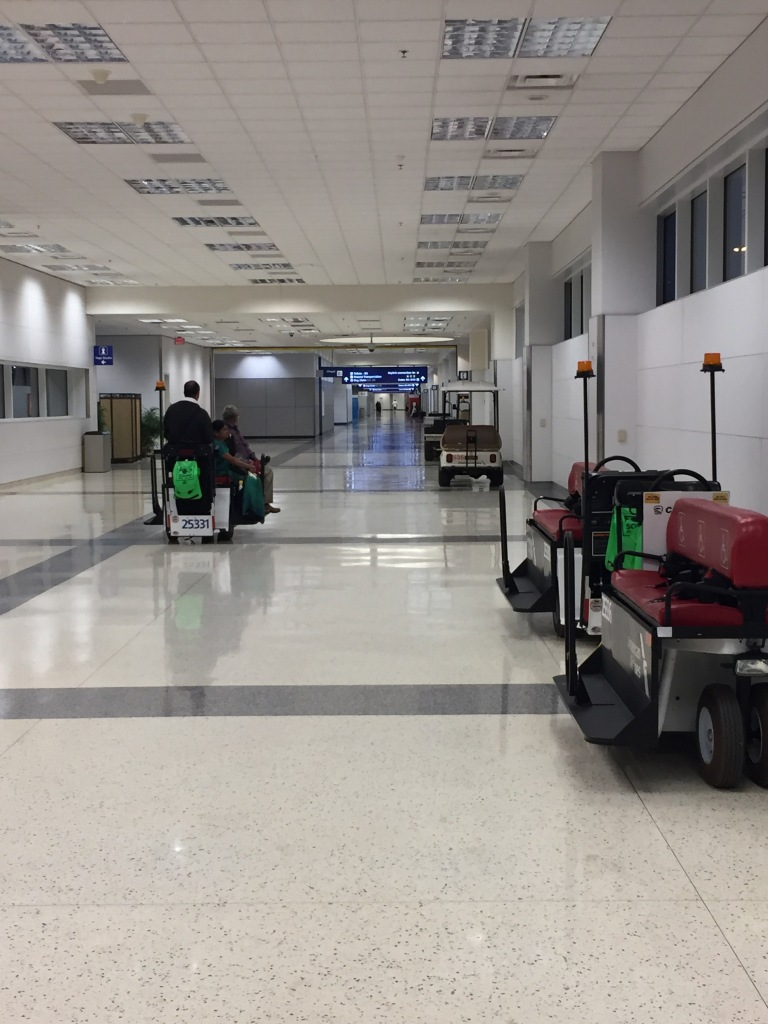 A quiet corridor of carts at DFW airport. Most are resting, and one is still on duty.