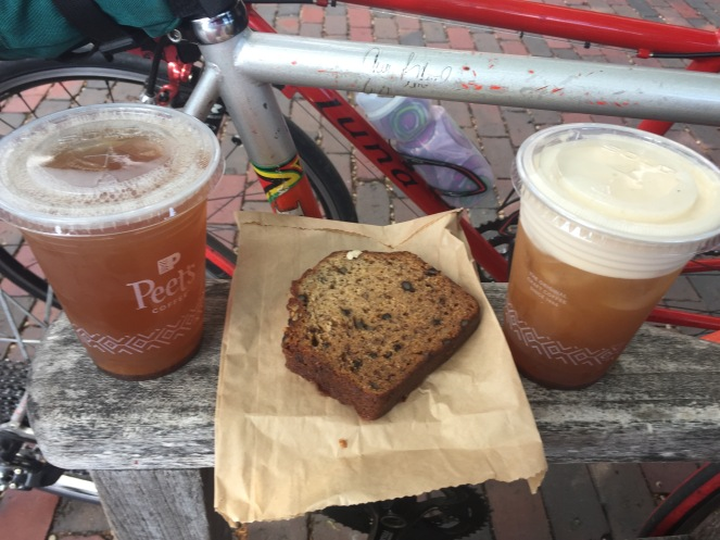 Two ice teas and one slice of banana bread, with two bikes waiting patiently behind.