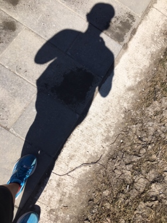 mage description: Tracy's shadow on sidewalk, dry mud beside, running shoes and lower legs visible in bottom left corner.