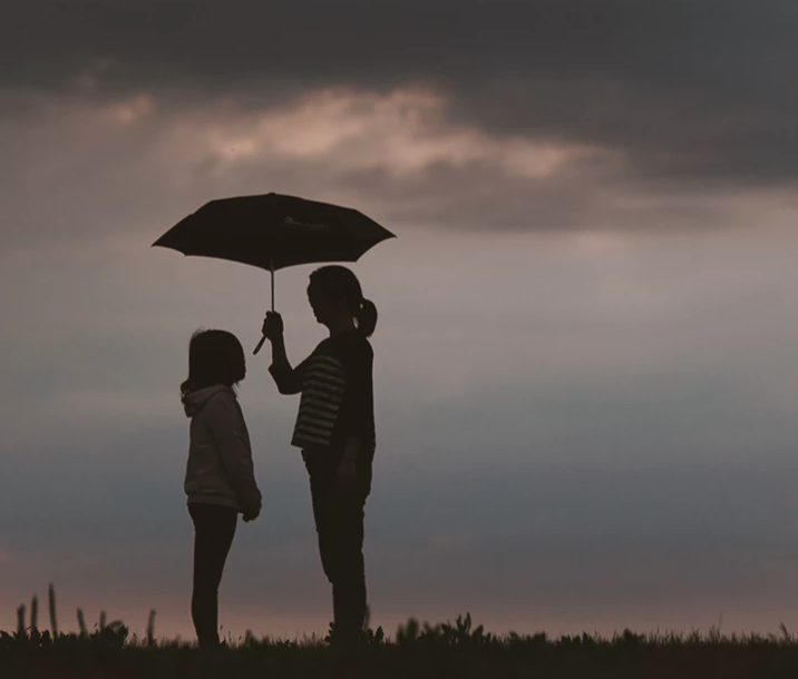 A child and adult-- the adult is holding an umbrella over the child.
