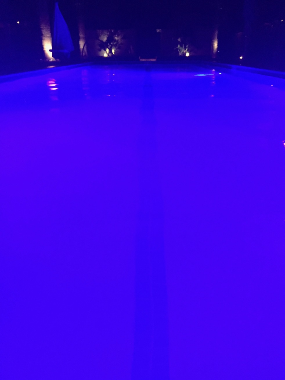 A blue pool at night.