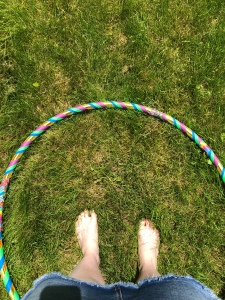 A blue, green, and gold hula hoop sits on the grass, a pair of feet with gold polish on the toenails are in the centre of the hoop.