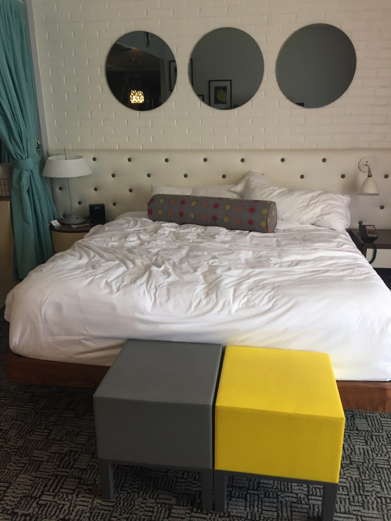 A king-sized bed in a midcentury-modern designed hotel room.