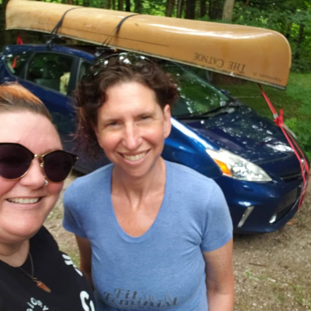 Susan and Jenn standing in front of Susan's blue Prius V with a yellow canoe trapped professionally to the top. Susan is wearing a blue shirt with the blog name on it.