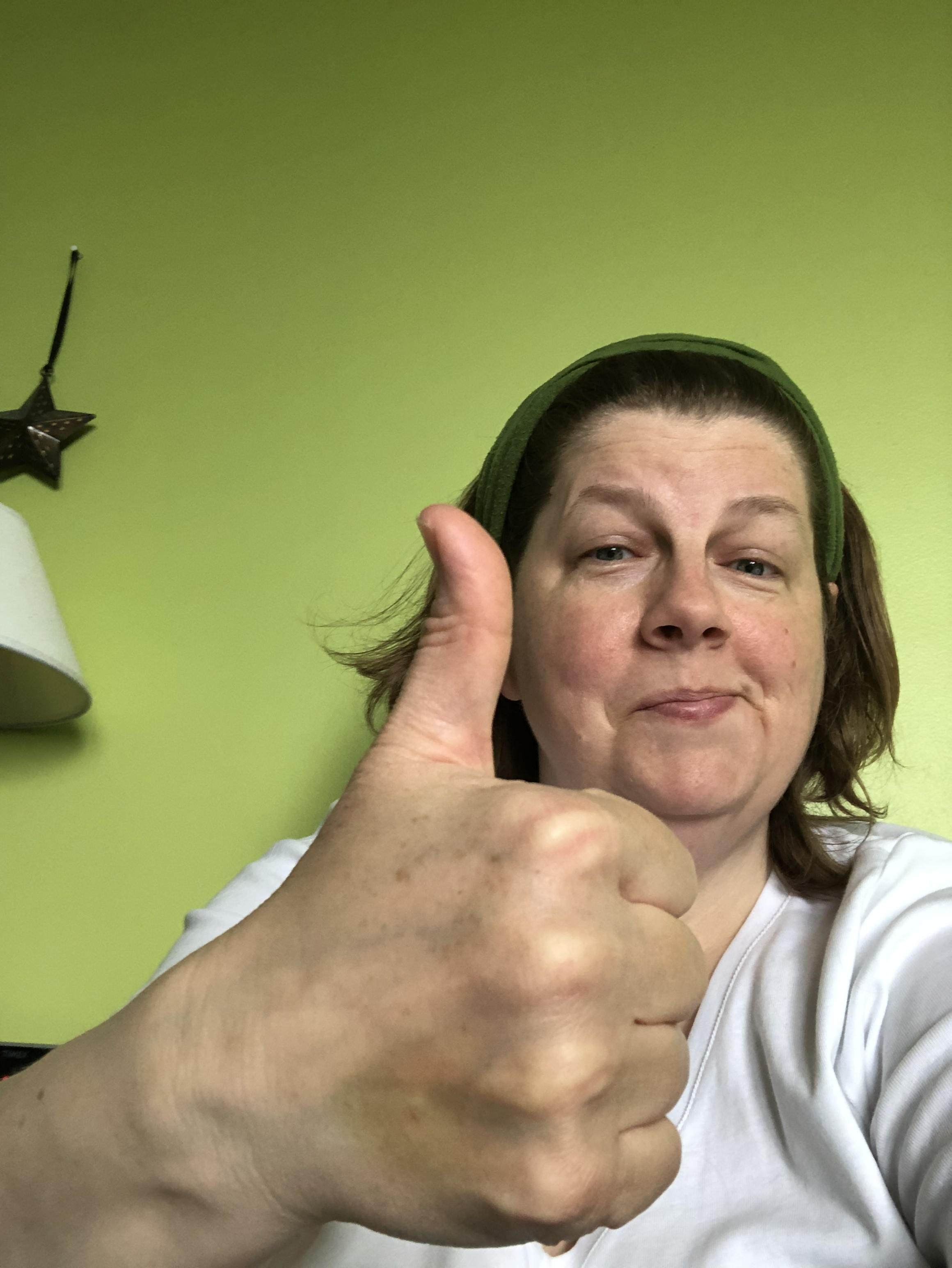A white woman wearing a white v-necked shirt is in front of a light green wall. She is smirking and she is giving a thumbs up with her right hand.