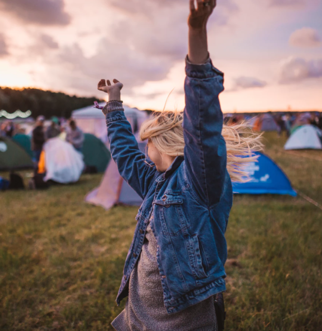 WWoman with hands in the air, presumably dancing. by Unsplash.