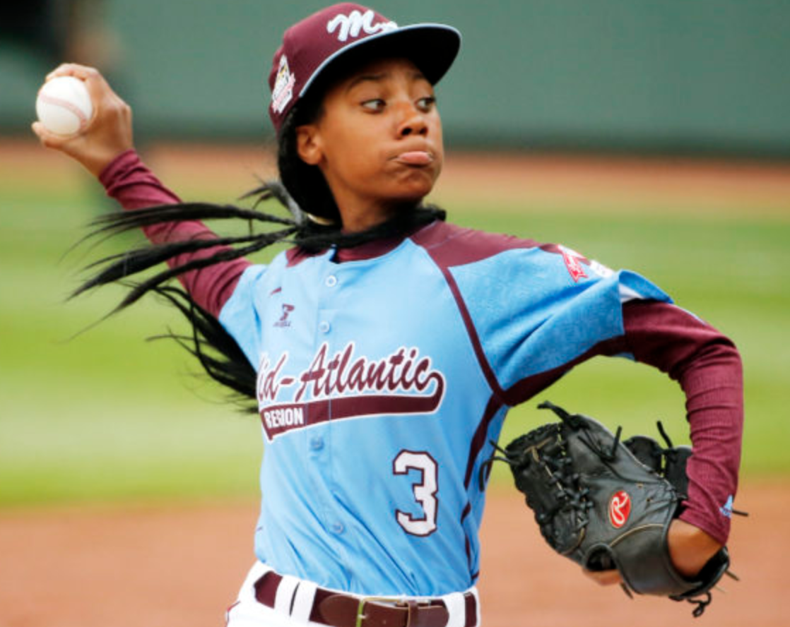 A girl, throwing a heater over the plate.