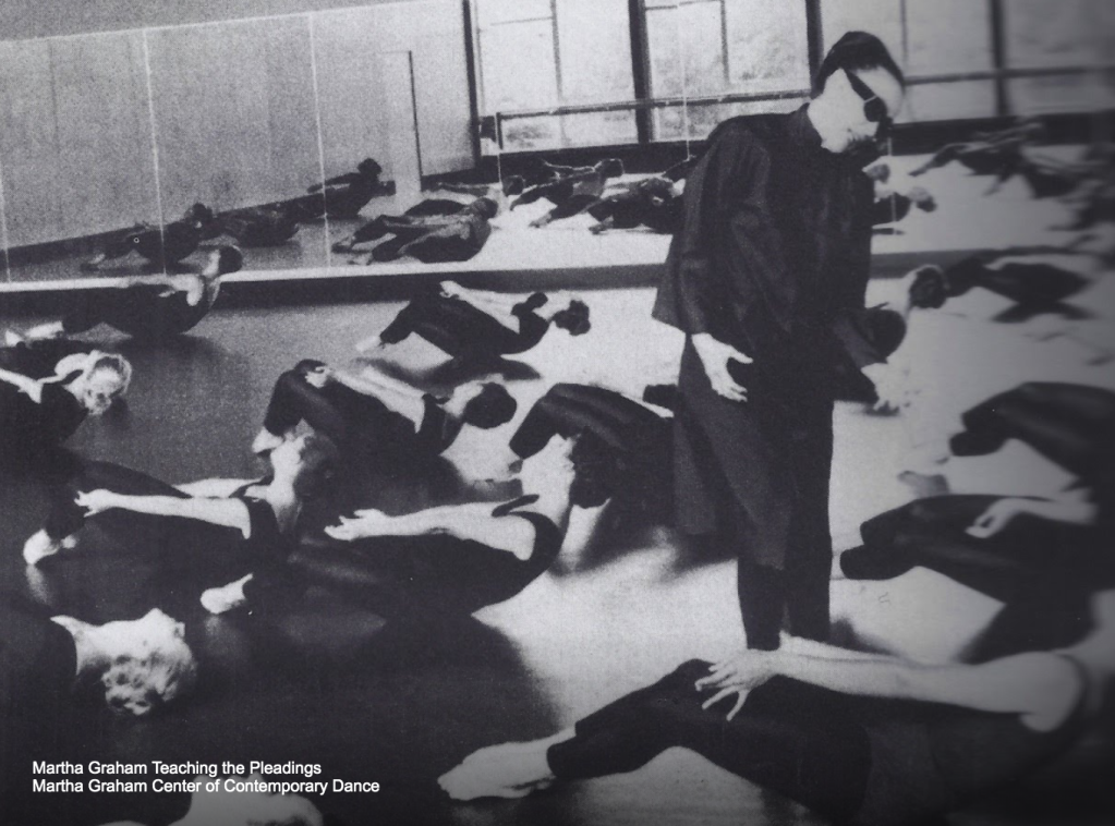 Students doing abdominals technique, with Martha Graham looming over them.