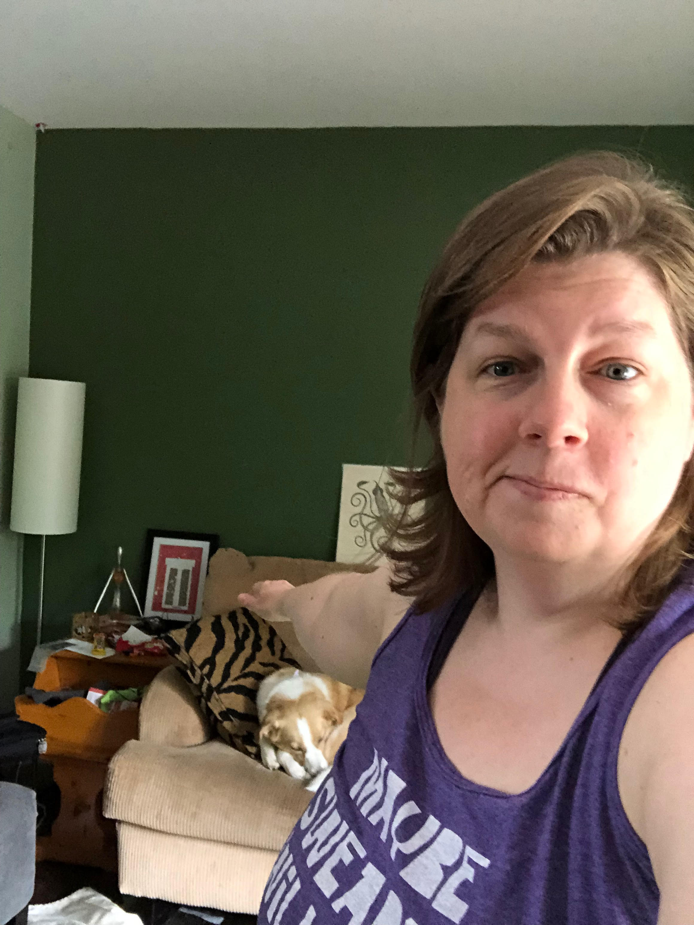 A middle aged white woman with shoulder-length light brown hair, wearing a purple tank top, smirks at the camera, behind her is a green wall, a beige couch and an endtable with knickknacks on it, there is a light brown dog asleep on the couch,  The woman's right hand is extended back away from the camera, in the position for Warrior II in yoga.
