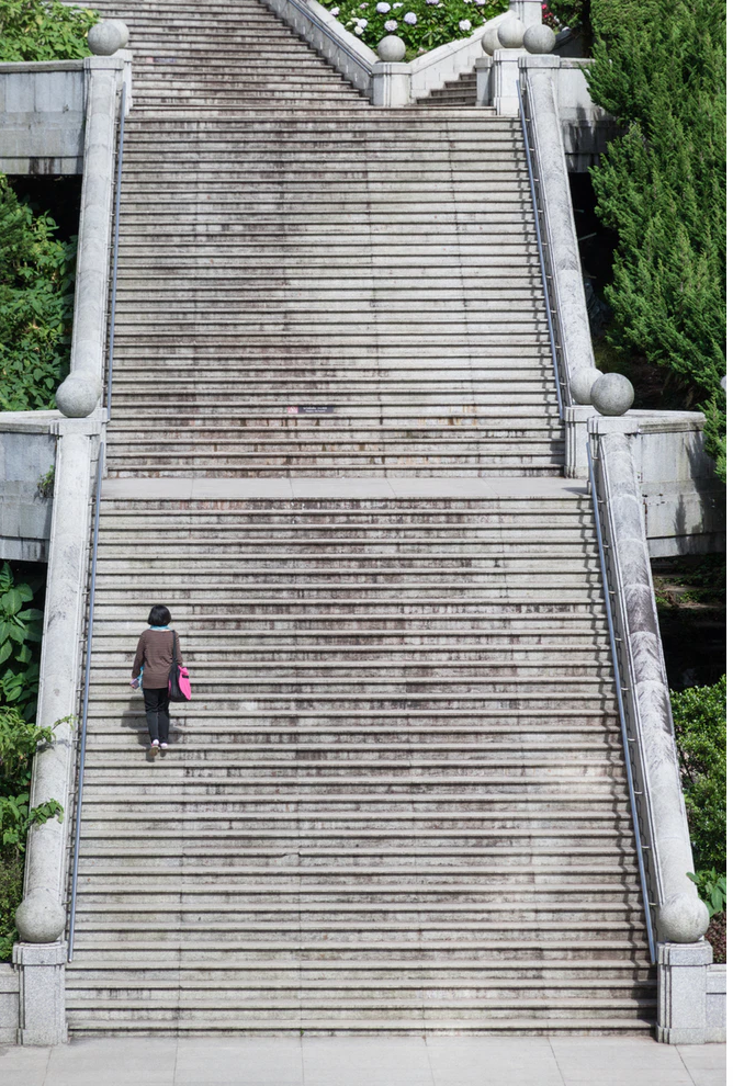 A woman with a pink bag, climbing a long staircase by herself.
