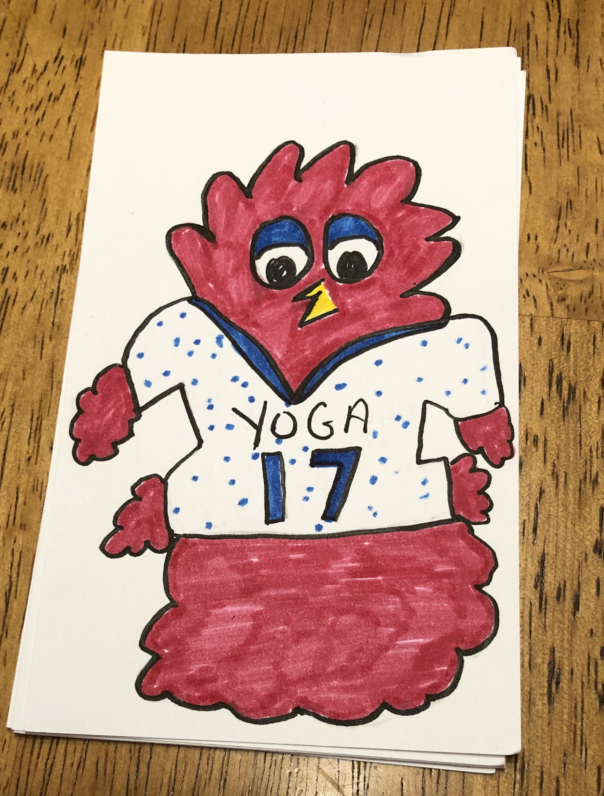 A drawing of a red fluffy monster with a beak, wearing a sports jersey that says 'Yoga 17'
