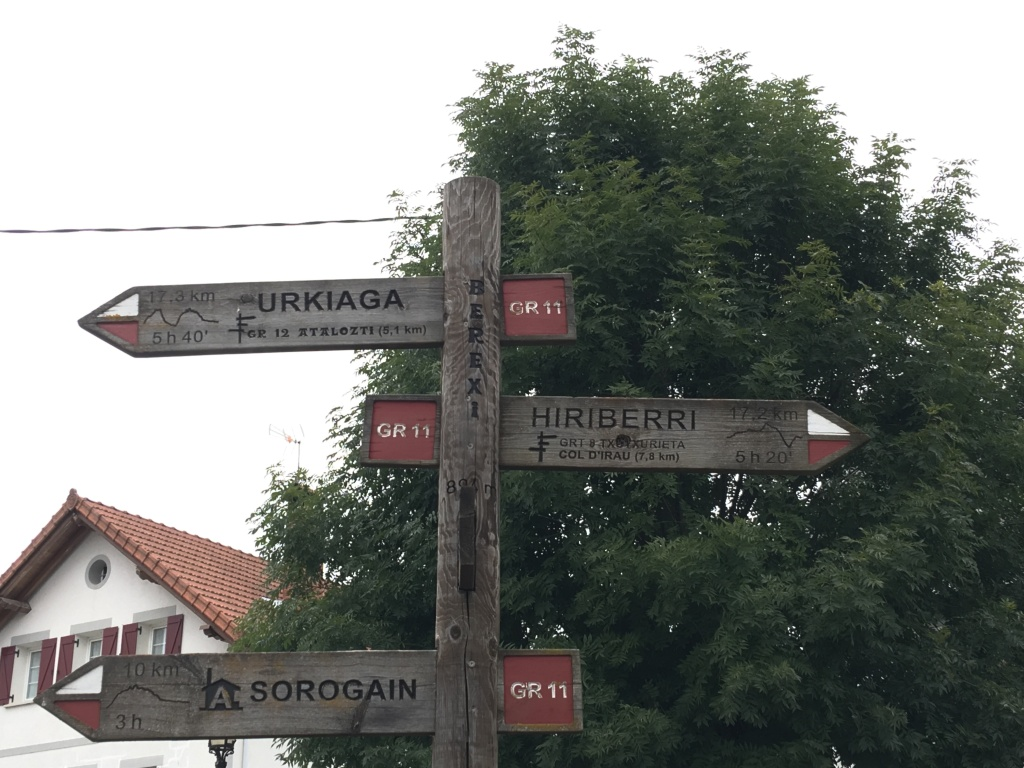 "a pole with arrow-shaped wooden signs pointing in different directions saying ""GR11"" and the names of different villages."