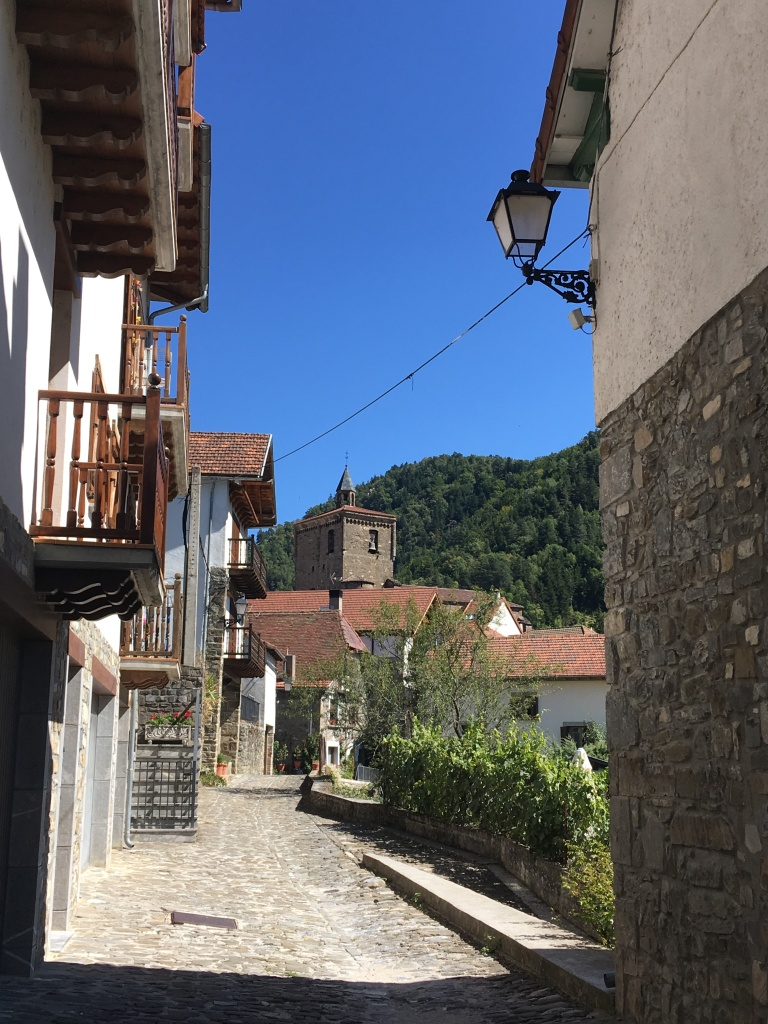 A narrow cobbled street lined with traditional houses with wooden balconies on the left. A square stone church tower in the background and forest-lined mountains in the background.
