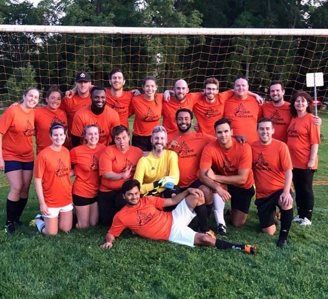 A motley group of 15 people wearing bright orange jerseys pose in front of a soccer net making silly faces.