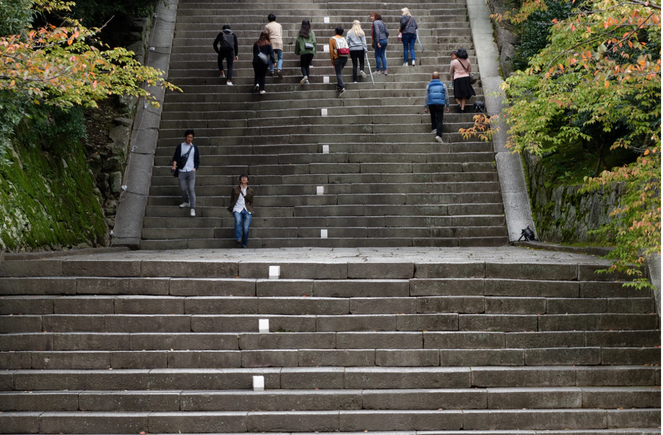 People walking up and down a long staircase.