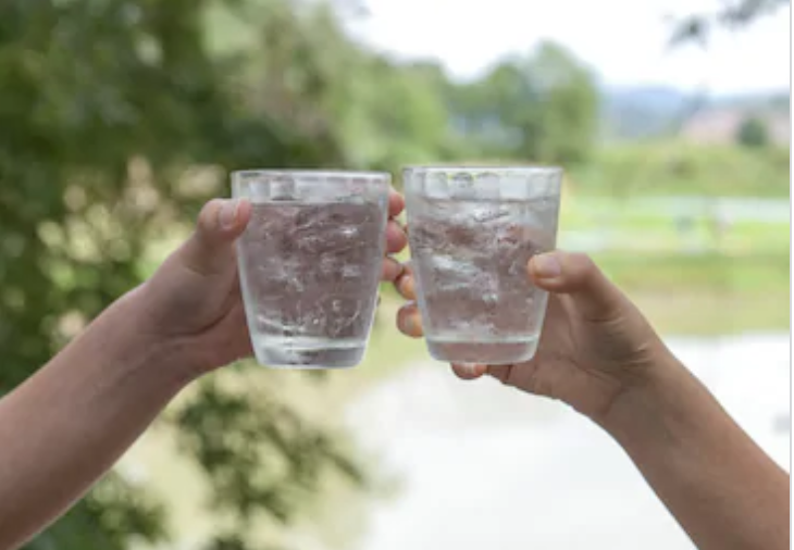 Two people, toasting with glasses of ice water.