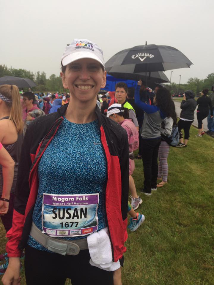 A white woman in a blue shirt with a white ball cap and running gear smiling because she just ran 21 km.