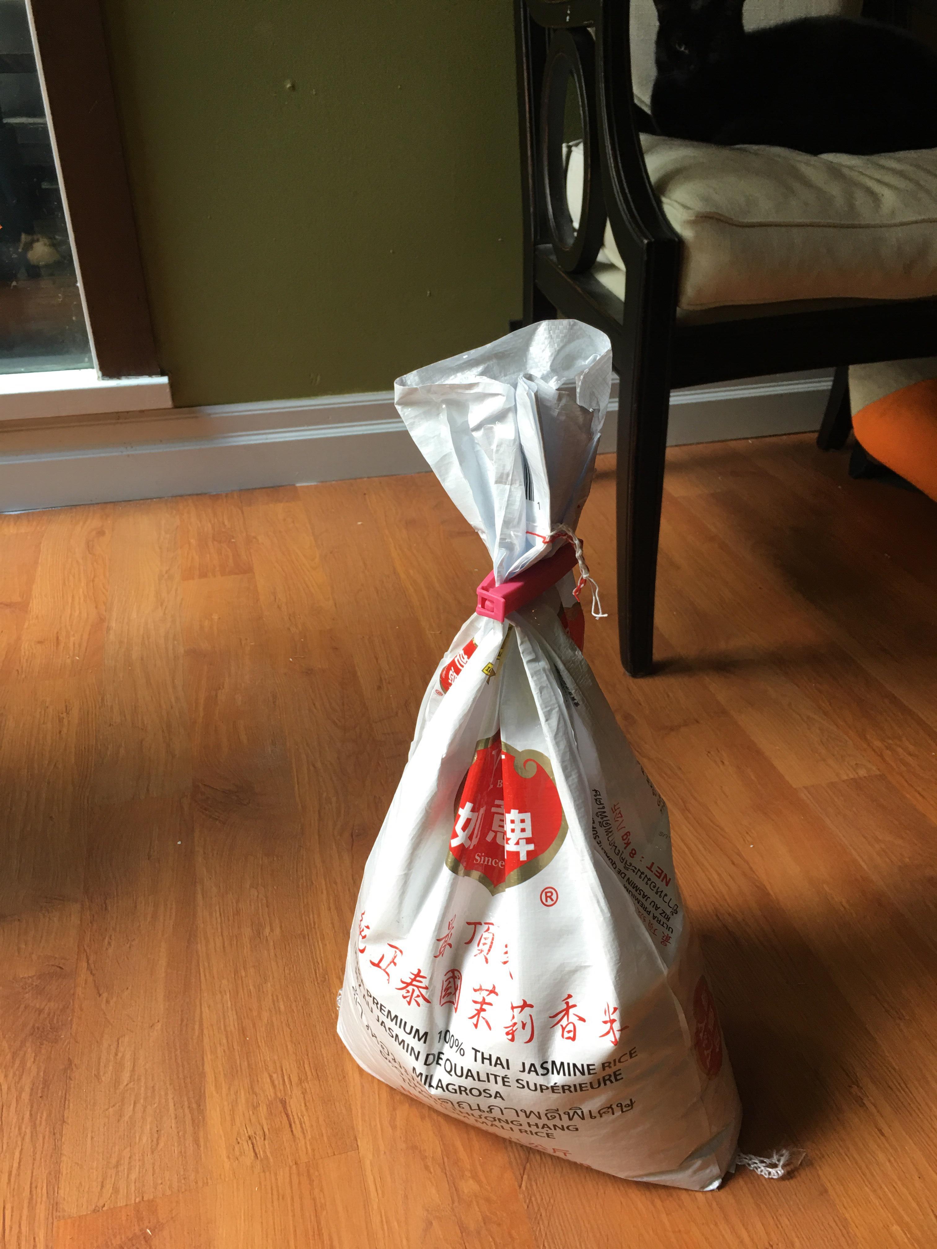 An 8 kilogram bag of jasmine rice sits on a slightly dirty floor