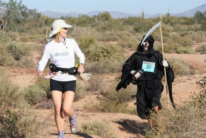Trail running race with a woman, followed by the grim reaper (in costume)