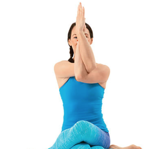 Seated eagle pose-- arms are crossed in front of your chest, intertwined with palms together.