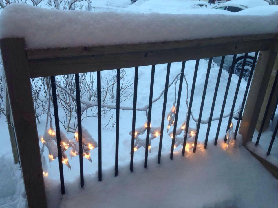 A snow covered porch rail is decorated with a string of large white plastic stars that are outlined with white lights.